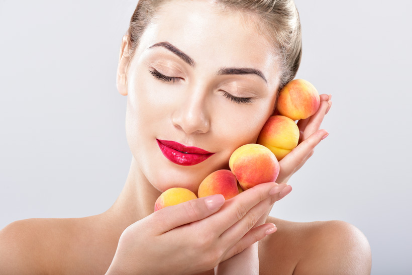 Beautiful woman holding a juicy apricots, peaches