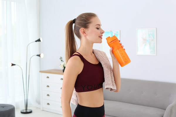 Woman drinking protein shake in living room