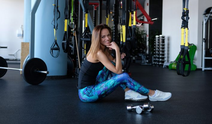 Fitness girl sitting on a floor